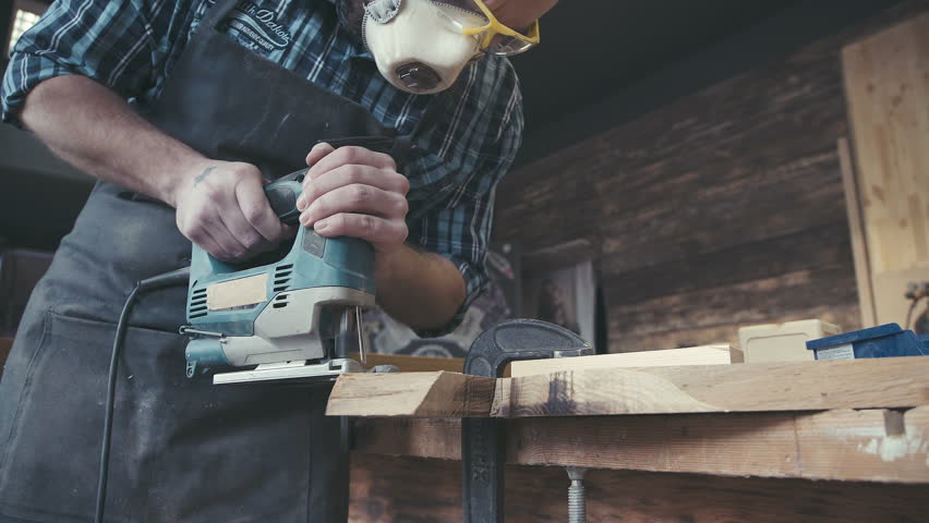 Joiner works with an electric jigsaw and processes wooden products. Joiner labouring in mask and glasses for safety. Carpenter with chisel in the hands on the workbench.