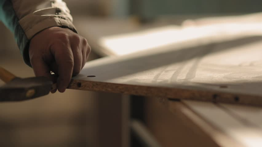 A man assembles furniture with hammer and nails | Shutterstock HD Video #24199456