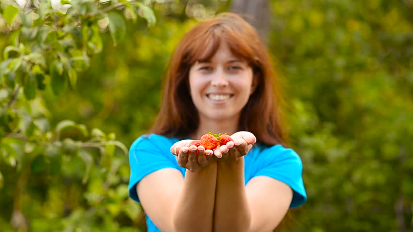 Strawberries red ripe holds in his hands the girl in a garden and smiling. Harvest season vitamin and sweet strawberries. Dietary and healthy products.