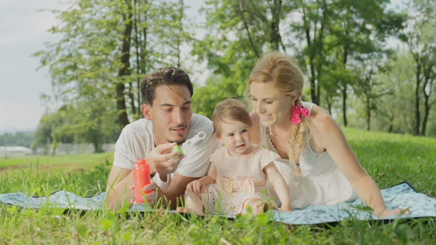 SLOW MOTION CLOSE UP, DOF: Cute happy young family lying on blanket on grass in park and playing. Cheerful dad blowing bubbles, beautiful blonde mother smiling and sweet baby girl sitting and giggling