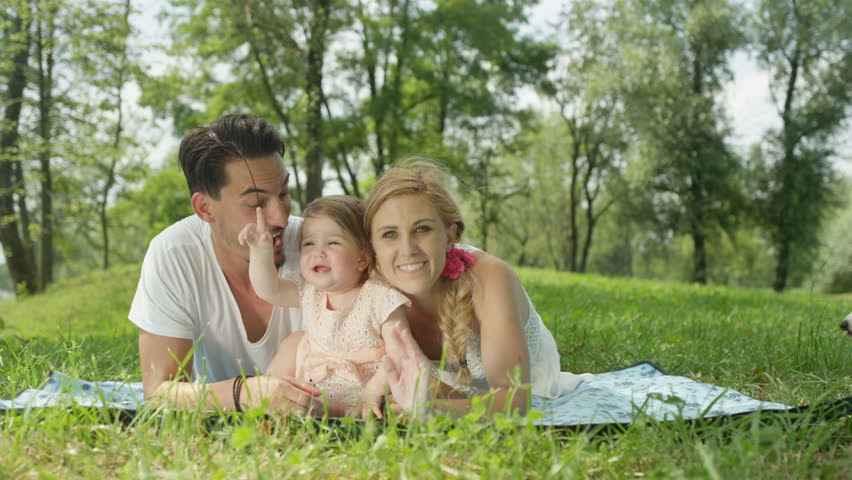 SLOW MOTION CLOSE UP DOF: Happy young mum and dad lying on the grass in park on beautiful day and caressing cheerful sweet baby girl in pinky dress. Idyllic family video calling and waving into camera | Shutterstock HD Video #24224581