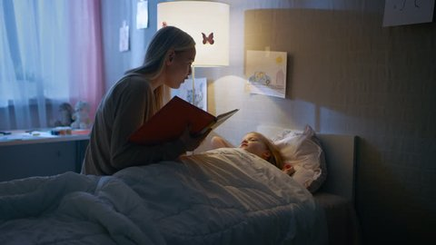 Young Loving Mother Reads Bedtime Stories to Her Little Beautiful Daughter who Goes to Sleep in Her Bed. Shot on RED EPIC-W 8K Helium Cinema Camera.