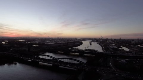Atmospheric aerial shot of the river Elbe and harbor of Hamburg. Shot in the evening with beautiful light. View of the skyline of Hamburg.