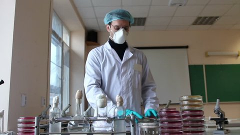 Scientist works  in microbiological scientific and education laboratory. Laboratory shaker, tubes, and  petri dishes stacks. Man turns on shaker and watches the petri dishes. Slider dolly shot.