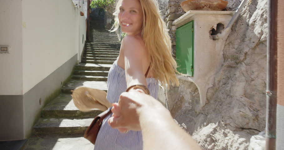 Young couple holding hands woman leading boyfriend up steps running through street  in Italian town POV travel concept Amalfi Coast Positano Italy