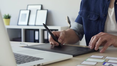 Closeup of freelance graphic designer sketching on tablet, working from home office.