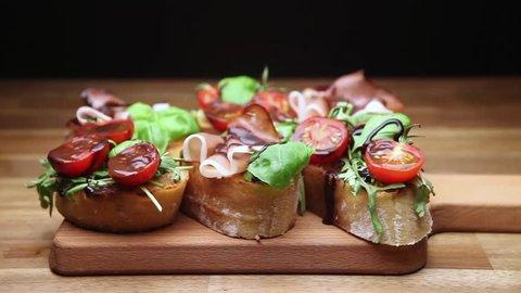 antipasto with ham jamon serrano, cherry tomatoes, arugula on wooden board