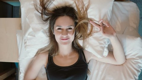 Happy young woman falls on the bed. Girl smiling, opens her eyes and looking to the camera.