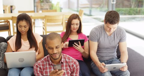 4K Group of friends relaxing at home, all engrossed with their mobile devices. Slow motion