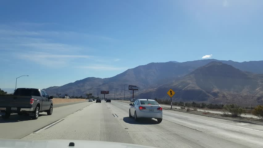 Driving by a large field of wind power generators on interstate joshua tree california united states of america november 6 driving on road sciox Choice Image