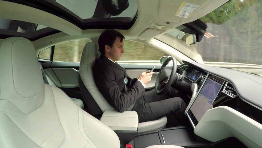 CLOSE UP: Young businessman texting writing messages on mobile phone while sitting behind self-driving steering wheel in autonomous autopilot driverless electric car traveling along countryside road #24320456