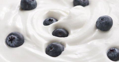 Blueberries in organic yogurt rotating loop video, 4k