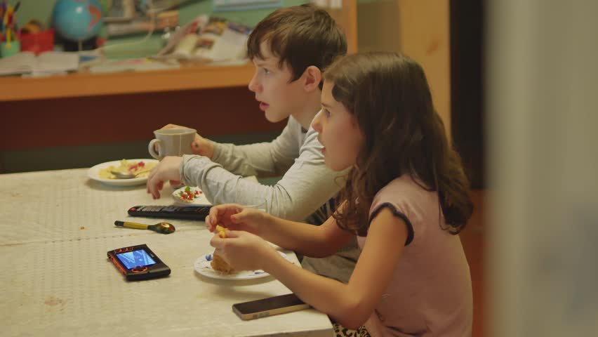 kids watching tv and eating. boy and girl family lifestyle children are eating at table, drink tea eat cake kids watching tv