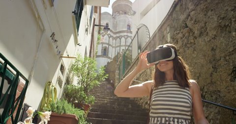 Woman exploring Italian town wearing virtual reality headset watching 360 travel video imagination concept  in Italian street  Ravello Amalfi Coast Italy