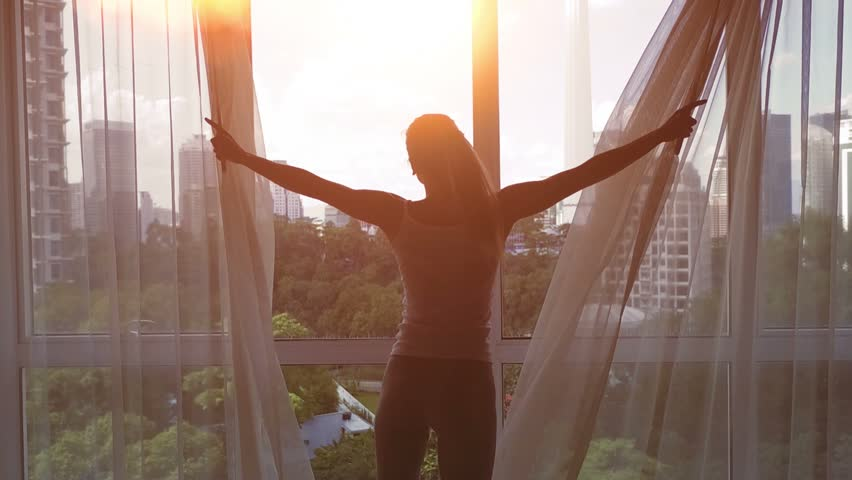 Slow motion. Young woman uncover the big window and looking out her apartment on the city buildings. Sunrise in the city. | Shutterstock HD Video #24373256