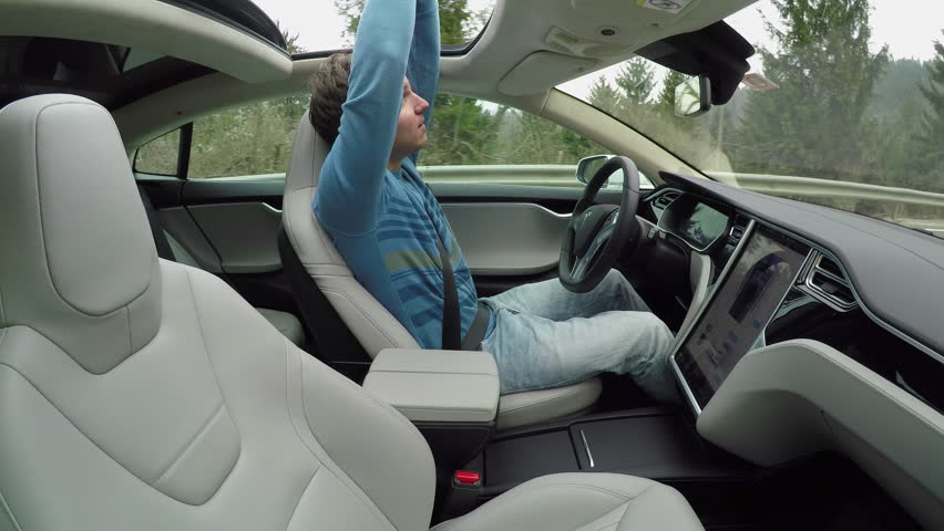 AUTONOMOUS TESLA CAR, FEBRUARY 2016:  Male driver enjoying ride with hands raised in self-driving autonomous autopilot Tesla Model S driverless car. Man sticking arms out of panoramic sunroof #24380066