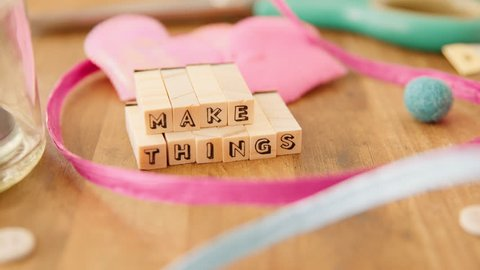 A woman's hand completes an inspiring message, made out of wooden letter blocks, at her wooden craft table, bursting with pretty craft supplies, in her artists' studio. Make Things.