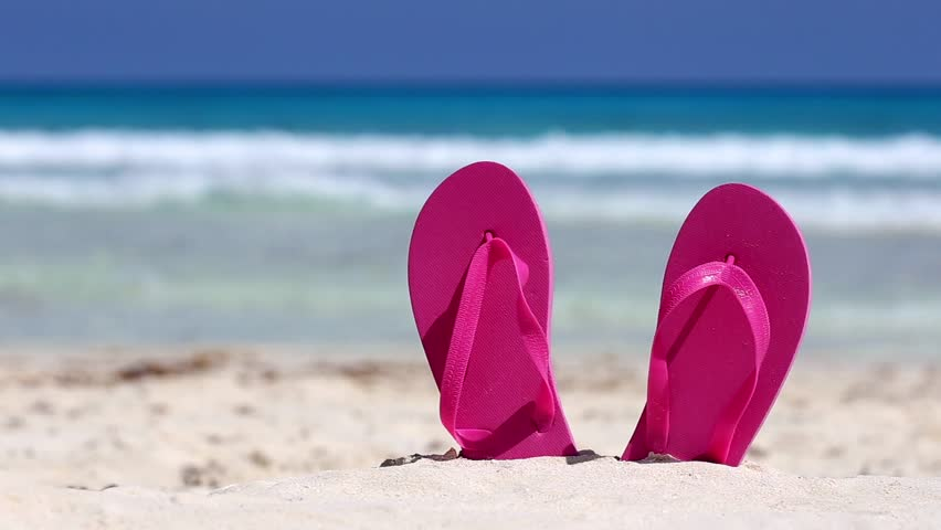 Pink flip flops on white sandy beach near caribbean sea, nobody. Summer vacation concept