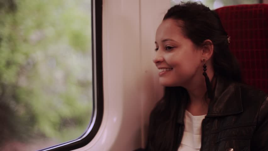 Happy train passenger traveling sitting in a seat and looking through the window - Young woman traveling by train | Shutterstock HD Video #24408776