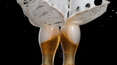 Having a toast with two glasses of beer and spilling. Shot with high speed camera, phantom flex 4K. Slow Motion.