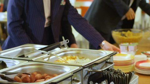 pupils take plates and put food into them in school canteen