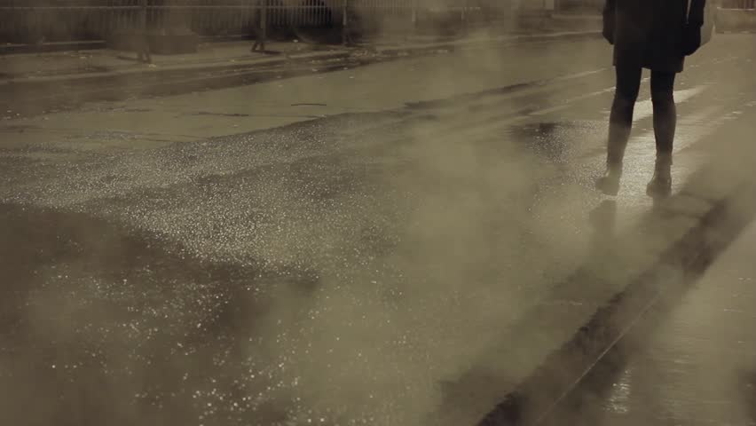 Person in black walk on city street covered by steam, carefully touch asphalt
