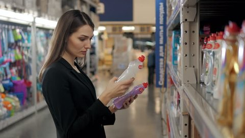 Woman choosing laundry detergent in grocery store. Businesswoman in supermarket