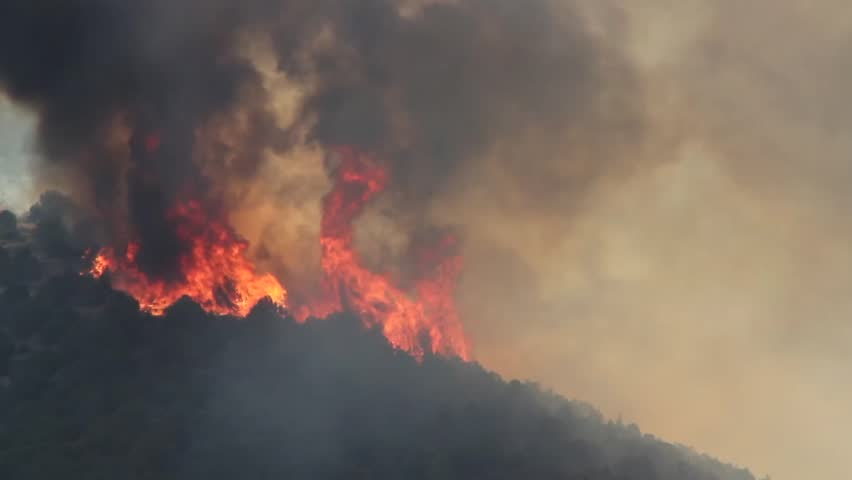 A raging wildfire burns across the mountain leaving a trail of smoke and ash.
