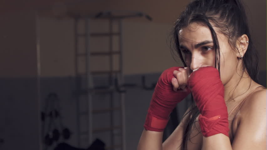 Beautiful girl in boxing gloves pushes the bag on a black background. Slow motion. | Shutterstock HD Video #24513146