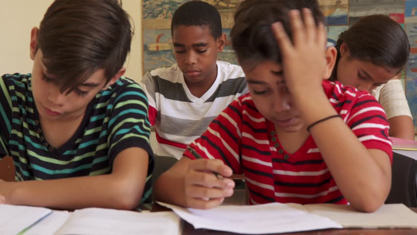 Young people and education. Group of hispanic students in class at school during lesson. Frustrated boys cheating during admission test, examination