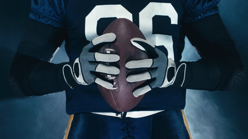 4K CINEMAGRAPH - seamless loop. EXTREME CU Caucasian male American football player holding a ball. RAW edited footage