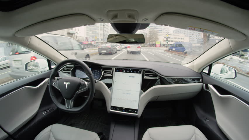 LJUBLJANA, SLOVENIA - FEBRUARY 4, 2017: Absolutely autonomous self-driving autopilot Tesla Model S driverless car driving by itself with no driver through crowded urban street in complex environment