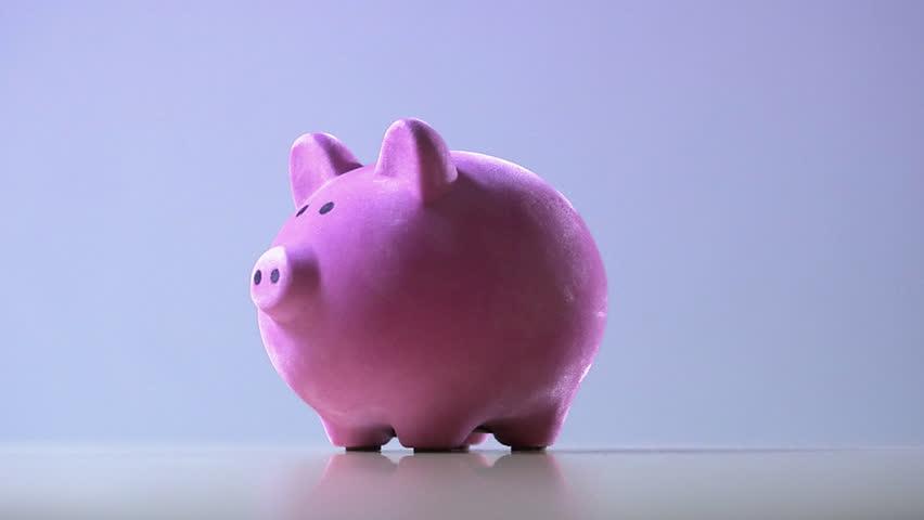A man putting coins in a piggy bank | Shutterstock HD Video #2458826