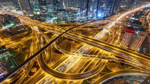 Spectacular nighttime skyline of downtown Dubai. Scenic aerial view of big highway intersection. 4K time lapse.