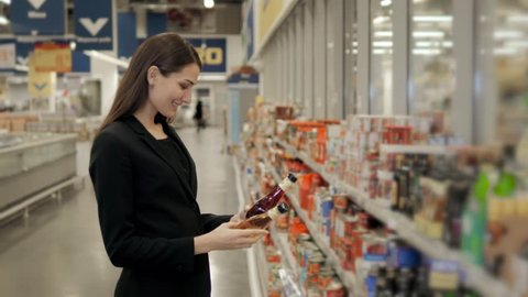 Portrait of positive woman girl buying conserve tomato sauce or balsamic vinegar in grocery shop