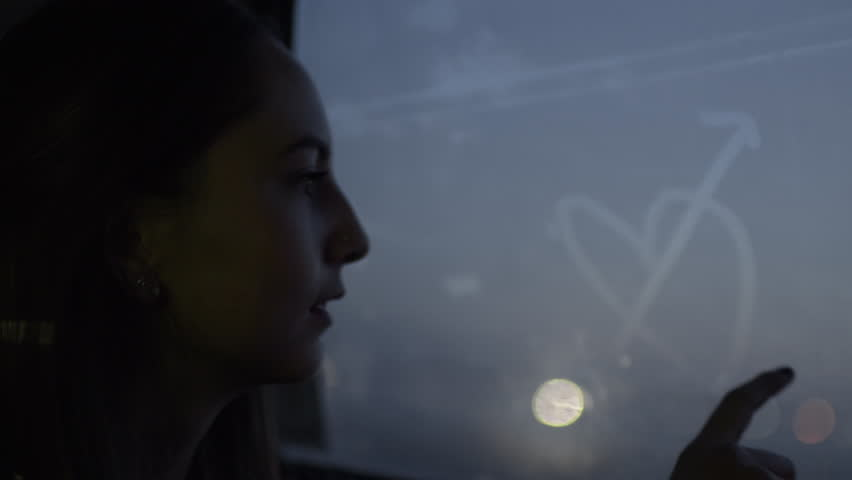 """Closeup Of Happy Teen Drawing A Heart (With Arrows Through It) And Writing The Word """"Love"""" On Foggy Window In Moving Car"""