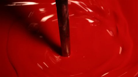 close up shot of the vat full of red paint is stirring