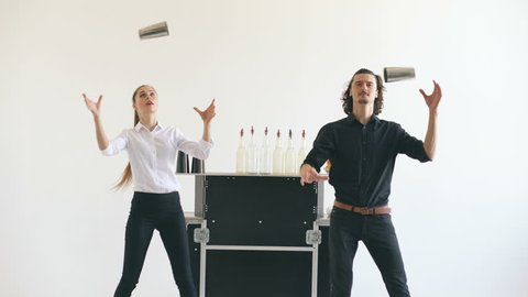 Professinal bartender man and woman juggling bottles and shaking cocktail at mobile bar table on white background
