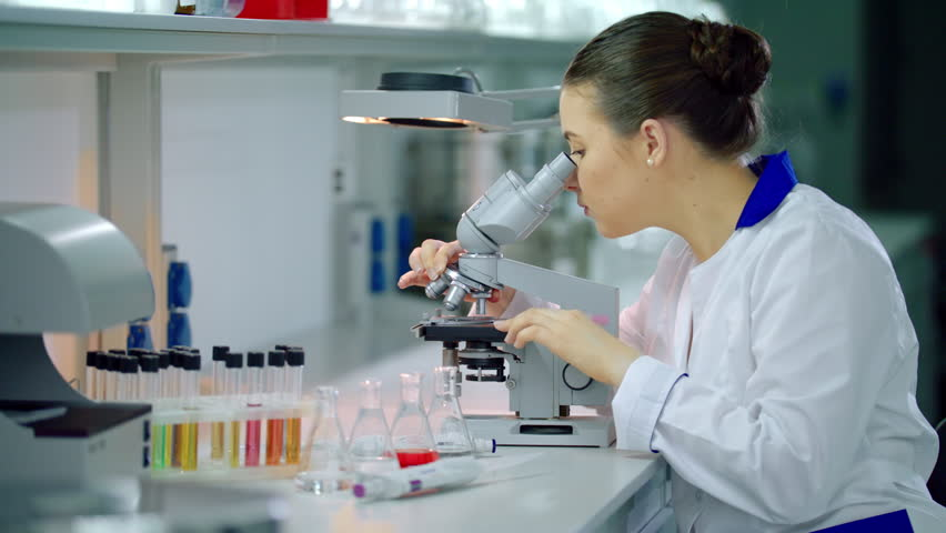 Female scientist with microscope in lab. Woman scientist doing microscope research. Microscope scientist working in lab. Lab scientist looking in microscope. Science laboratory research | Shutterstock HD Video #24615257