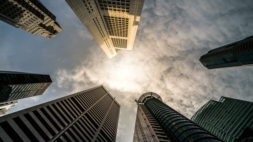 Time lapse - Looking up to business and financial skyscraper buildings in Singapore with moving clouds and sun in the sky.
