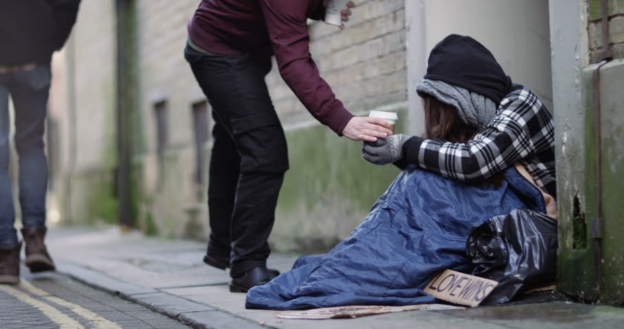 4k, Man hands over a hot drink to a homeless woman.