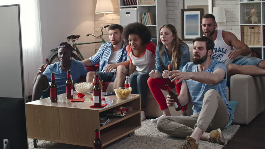 Zoom in of multi-ethnic group of friends celebrating victory of their team. They yelling, clapping hands and whistling while sitting in living room and watching TV match