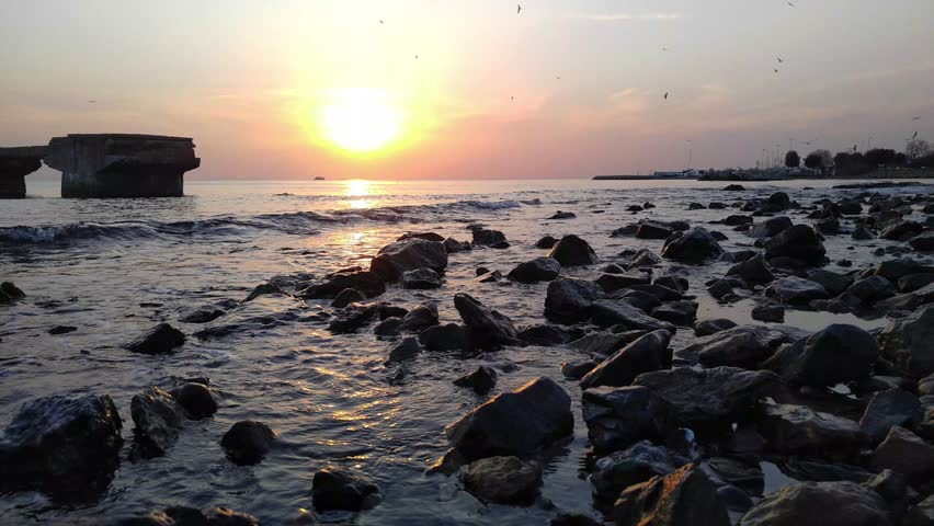 Sunset time at the beach.Waves reaches to the shore between the rocks.