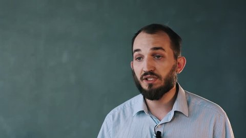Young caucasian bearded businessman in striped shirt with lavalier microphone on isolated background wall passionatly speaking