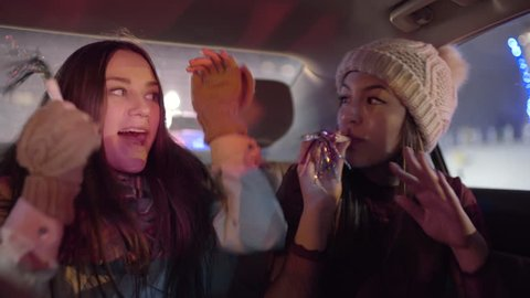 Young Women Celebrate In Backseat Of Moving Car, They Dance And Sing And Blow Party Blowers