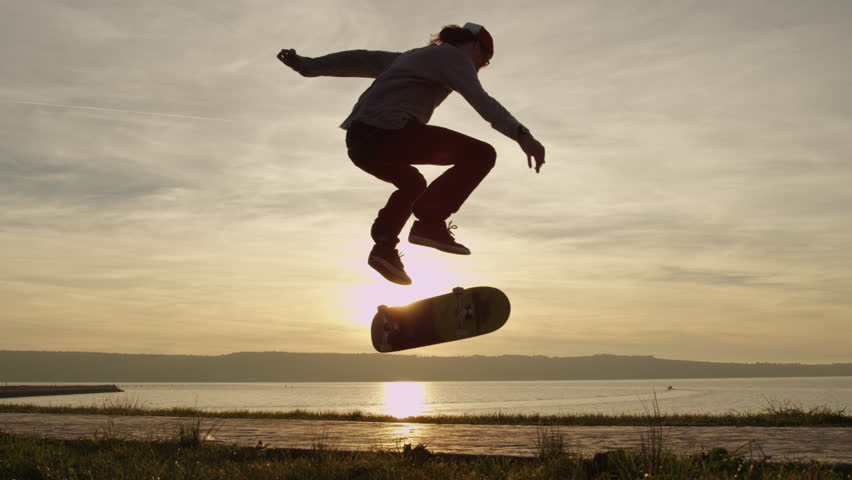 SLOW MOTION CLOSE UP, DOF: Silhouetted skateboarder skateboarding and jumping kickflip trick on walking path along the ocean coastline against golden setting sun. Skater riding skateboard doing tricks