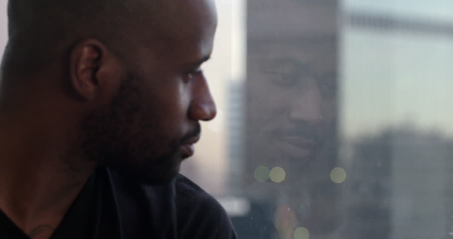 Handsome African American man looks past his reflection in window overlooking the Downtown Los Angeles skyline.  Big close up, recorded in slow motion at 60fps.