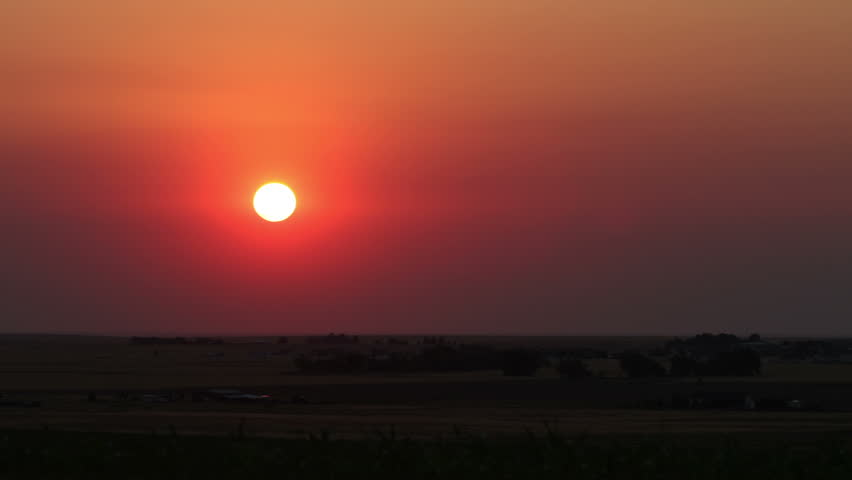Sunrise on the plains, obscured by smoke from a brush fire in the summer heat and drought conditions. HD 1080p time lapse.