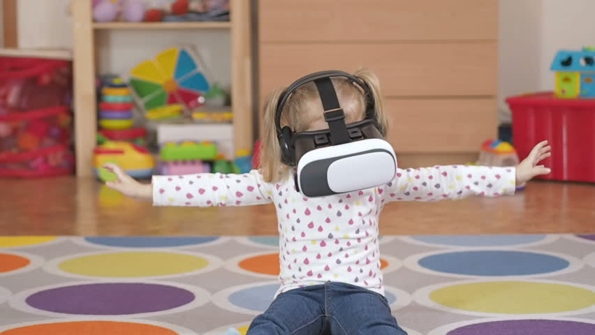 Girl wearing virtual reality goggles. Virtual reality game. The little girl with surprise and pleasure uses head-mounted display.
