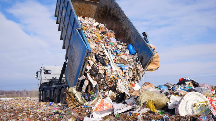 Garbage truck disposed trash on the landfill. Vehicle transporting garbage to waste.